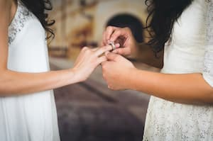 Two brides exchanging rings